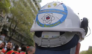 """FILE - In this file photo dated Thursday, April 6, 2017, a sticker is photographed on a helmet of an employee of Fessenheim's nuclear power plant opposing the closure, during a protest outside the EDF headquarters in Paris, France. A statement released Wednesday Feb. 19, 2020, that Fessenehim will close one of its reactors on upcoming Saturday, as the first phase of a shut-down at the plant.  Sticker on helmet reads, """"Fessenheim's power plant secure, yes to the nuclear"""". (AP/Photo Michel Euler, FILE)"""