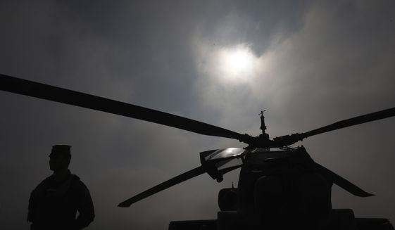 A marine stands in front of an helicopter during a drill at a military base in Stefanovikio, central Greece on Wednesday, Feb. 19, 2020. Army aviation forces from Greece and the United States are taking part in a live-fire exercise with attack helicopters, marking deepening defense ties between the two countries. (AP Photo/Yorgos Karahalis)