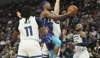 Charlotte Hornets' Devonte' Graham, center, drives between Minnesota Timberwolves' Naz Reid, left, and another defender during the second half of an NBA basketball game Wednesday, Feb. 12, 2020, in Minneapolis. (AP Photo/Jim Mone)