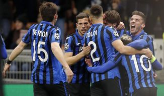 Atalanta players celebrate after Atalanta's Hans Hateboer scored his side's opening goal during the Champions League round of 16, first leg, soccer match between Atalanta and Valencia at the San Siro stadium in Milan, Italy, Wednesday, Feb. 19, 2020. (AP Photo/Antonio Calanni)