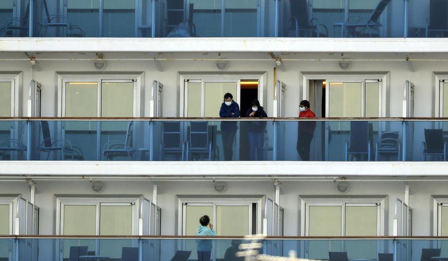 Passengers speak on balconies of the quarantined Diamond Princess cruise ship docked at a port in Yokohama, near Tokyo, Thursday, Feb. 20, 2020. Passengers tested negative for COVID-19 started disembarking since Wednesday. (AP Photo/Eugene Hoshiko)