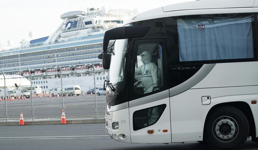 A buse carrying the passengers from the quarantined Diamond Princess cruise ship leaves a port in Yokohama, near Tokyo, Wednesday, Feb. 19, 2020. Hundreds of passengers began leaving the cruise ship Wednesday after the end of a much-criticized, two-week quarantine that failed to stop the spread of a new virus among passengers and crew. (AP Photo/Eugene Hoshiko)