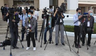 Media wear face masks to protect themselves from a new virus wait China's Foreign Minister Wang Yi's arrival at Wattay Airport for the Special ASEAN-China Foreign Ministers' Meeting on the coronavirus disease 2019 (COVID-19) in Vientiane, Laos, Wednesday, Feb. 19, 2020. (AP Photo/Sakchai Lalit)