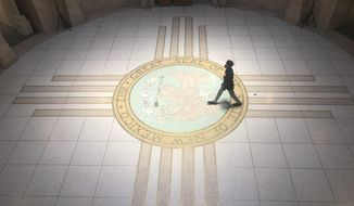 A staffer walks through the New Mexico Capitol Rotunda in Santa Fe, N.M., on Monday, Feb 17, 2020. State lawmakers are racing through bills before the session ends Thursday. (AP Photo/Russell Contreras)