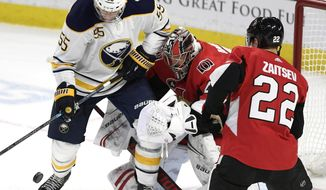 Buffalo Sabres defenseman Rasmus Ristolainen (55) tries to control the puck in front of Ottawa Senators goaltender Craig Anderson (41) and defenseman Nikita Zaitsev (22) during the third period of an NHL hockey game, Tuesday, Feb. 18, 2020 in Ottawa, Ontario. (Justin Tang/the Canadian Press via AP)