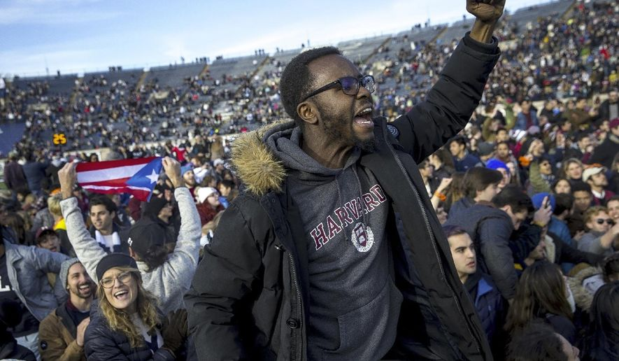 FILE - In this Nov. 23, 2019, file photo, Harvard and Yale students protest during halftime of the NCAA college football game between Harvard and Yale at the Yale Bowl in New Haven, Conn. Students alarmed by climate change are stepping up pressure on universities to stop investing in fossil fuel industries and are gaining wider traction in 2020. (Nic Antaya/The Boston Globe via AP, File)