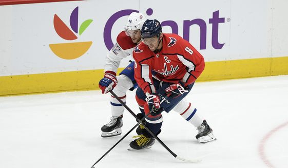 Washington Capitals left wing Alex Ovechkin (8), of Russia, battles for the puck with Montreal Canadiens left wing Jonathan Drouin (92) during the first period of an NHL hockey game, Thursday, Feb. 20, 2020, in Washington. (AP Photo/Nick Wass)