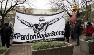 """Supporters of Roger Stone with a banner that reads """"#PardonRogerStone"""" wait outside federal court in Washington, Thursday, Feb. 20, 2020. President Donald Trump loyalist and ally, Roger Stone was sentenced to over three years in federal prison, following an extraordinary move by Attorney General William Barr to back off his Justice Department's original sentencing recommendation. The sentence came amid President Donald Trump's unrelenting defense of his longtime confidant that led to a mini-revolt inside the Justice Department and allegations the president interfered in the case. (AP Photo/Manuel Balce Ceneta)"""