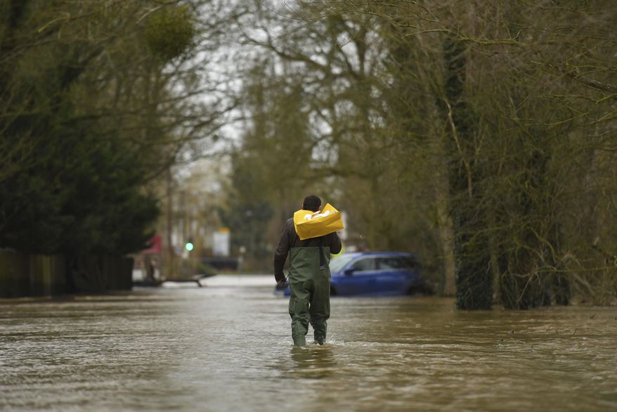 A man wades through flood water in the aftermath of Storm Dennis, in Upton-upon-Severn, England, Wednesday Feb. 19, 2020. Flood-hit communities are braced for further heavy rain as river levels continue to threaten to breach flood barriers, with some residential areas evacuated across Wales and western England.  (Jacob King/PA via AP)