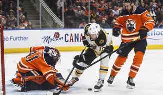 Boston Bruins left wing Anders Bjork (10) is stopped by Edmonton Oilers goalie Mike Smith (41) as Adam Larsson (6) defends during the first period of an NHL hockey game, Wednesday, Feb. 19, 2020 in Edmonton, Alberta. (Jason Franson/The Canadian Press via AP)