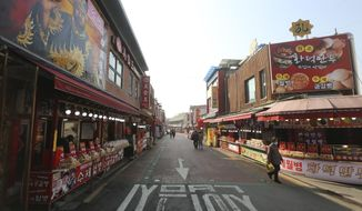 In this Feb. 14, 2020, photo, a woman wearing a face mask walks on a almost empty street at the Chinatown in Incheon, South Korea. Even as cases and deaths from the new virus mount, fear is advancing like a tsunami - and not just in the areas surrounding the Chinese city of Wuhan, the center of the outbreak that has been declared a global health emergency. A restaurant owner in the Chinatown says visitors have dropped by 90%. (AP Photo/Ahn Young-joon)