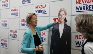 Democratic presidential candidate Sen. Elizabeth Warren, D-Mass., signs a cardboard cutout of herself at a campaign office, Thursday, Feb. 20, 2020, in North Las Vegas, Nev. (AP Photo/John Locher)