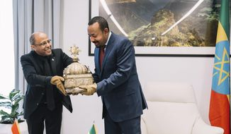 Ethiopia's Prime Minister, Abiy Ahmed, right, with gloved hands as he officially hands over a crown to the country's tourism minister, Hirut Kassaw, Thursday, Feb. 20, 2020.  The 18th Century Ethiopian crown has been returned home after being hidden in a Dutch flat for the past 21-years. (The Office of Prime Minister Abiy Ahmed via AP)