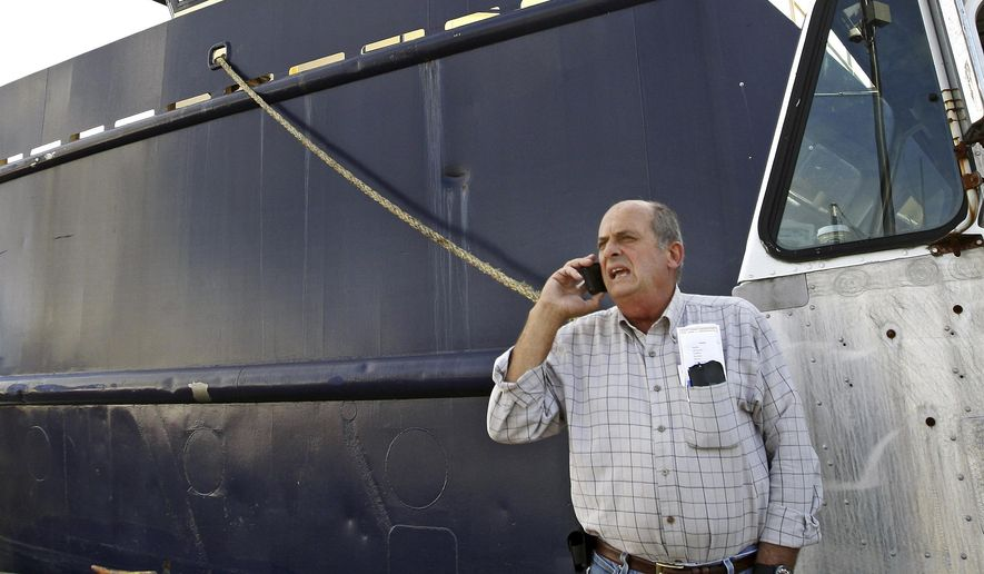 FILE - In this Oct. 14, 2014, file photo, Carlos Rafael talks on the phone at Homer's Wharf near his herring boat F/V Voyager in New Bedford, Mass. A Massachusetts company is slated to acquire in 2020 what's left of the boats once owned by Rafael, who was forced out of the industry after an elaborate fraud. The fishing magnate, known as the Codfather, was sentenced in 2017 to nearly four years in prison after pleading guilty to evading fishing quotas and smuggling money to Portugal. (John Sladewski/Standard Times via AP, File)