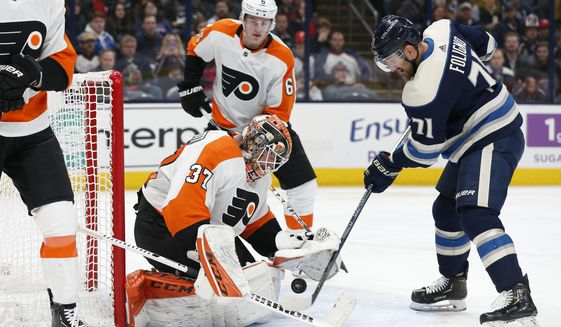 Philadelphia Flyers' Brian Elliott (37), left, makes a save against Columbus Blue Jackets' Nick Foligno, right, as Travis Sanheim waits for the rebound during the second period of an NHL hockey game Thursday, Feb. 20, 2020, in Columbus, Ohio. (AP Photo/Jay LaPrete)
