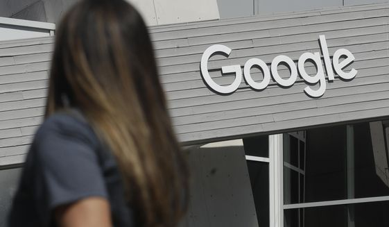 In this Sept. 24, 2019, file photo, a woman walks below a Google sign on the campus in Mountain View, Calif. (AP Photo/Jeff Chiu, File)