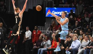 Miami Heat guard Duncan Robinson, front right, passes the ball after saving it from going out of bounds as Atlanta Hawks guard Kevin Huerter (3) defends during the first half of an NBA basketball game Thursday, Feb. 20, 2020, in Atlanta. (AP Photo/John Amis)