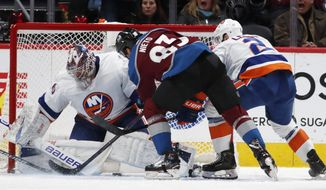 New York Islanders goaltender Semyon Varlamov, left, stops a shot by Colorado Avalanche left wing Matt Nieto as Islanderss defenseman Nick Leddy covers during the second period of an NHL hockey game Wednesday, Feb. 19, 2020, in Denver. (AP Photo/David Zalubowski)