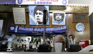 A bar tender prepares an espresso coffee inside the Bar Nilo where a makeshift shrine of soccer legend and former Napoli player Diego Armando Maradona is displayed, in downtown Naples, Italy, Wednesday, Sept. 18, 2019. Maradona achieved some of his most memorable exploits and in Naples is still revered with god-like status. (AP Photo/Gregorio Borgia)