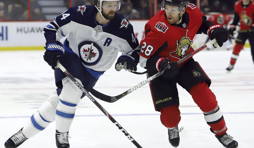Ottawa Senators right wing Connor Brown (28) and Winnipeg Jets defenseman Josh Morrissey (44) battle for position during the second period of an NHL hockey game, Thursday, Feb. 20, 2020 in Ottawa, Ontario. (Fred Chartrand/The Canadian Press via AP)