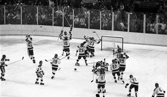 FILE - In this Feb. 22, 1980, file photo, the U.S. ice hockey team rushes toward goalie Jim Craig after their 4-3 upset win over the Soviet Union in a medal round match at the Winter Olympics in Lake Placid, N.Y. Some of the U.S. players shown are Mark Johnson (10); Eric Strobel (19); William Schneider (25); David Christian (23); Mark Wells (15); Steve Cristoff (11); Bob Suter (20) and  Philip Verchota (27).  (AP Photo/File)