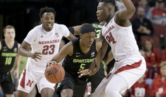 Michigan State's Cassius Winston (5) drives between Nebraska's Jervay Green (23) and Nebraska forward Yvan Ouedraogo (24) during the first half of an NCAA college basketball game in Lincoln, Neb., Thursday, Feb. 20, 2020. (AP Photo/Nati Harnik)