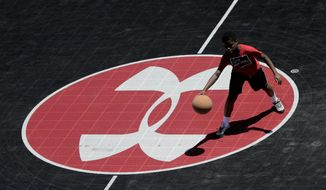 FILE - In this July 1, 2019, file photo the logo for Under Armour, which is based in Baltimore, is seen at half court as Neko Coleman, 10, plays basketball during a summer day at Federal Hill Park in Baltimore. Under Armour last week said it would up to $425 million in restructuring charges as it tries to reverse a decline in sales in 's latest warning about sales and costs put another dent in its stock price and added to a years-long decline. (AP Photo/Julio Cortez, File)