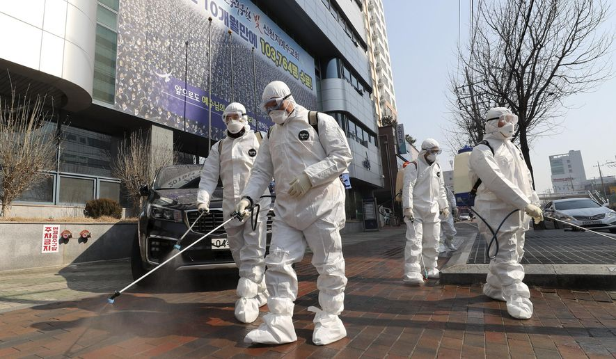 Workers wearing protective gears spray disinfectant against the new coronavirus in front of a church in Daegu, South Korea, Thursday, Feb. 20, 2020. The mayor of the South Korean city of Daegu urged its 2.5 million people on Thursday to refrain from going outside as cases of the new virus spike. (Kim Jun-beom/Yonhap via AP)