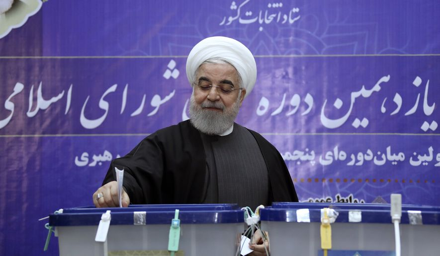 In this photo released by the official website of the office of the Iranian Presidency, President Hassan Rouhani casts his ballot in the parliamentary elections at the interior ministry in Tehran, Iran, Friday, Feb. 21, 2020. (Iranian Presidency Office via AP) ** FILE **