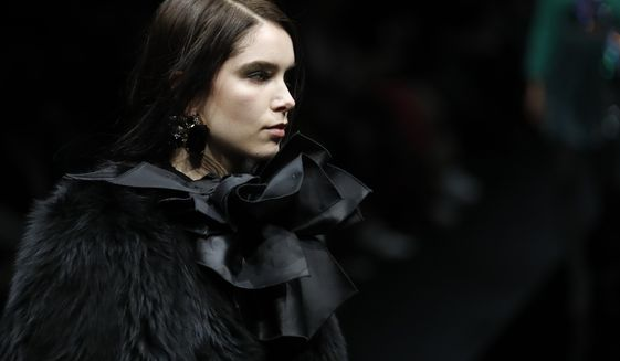A model wears a creation as part of Emporio Armani's Fall/Winter 2020/2021 collection, presented in Milan, Italy, Friday, Feb. 21, 2020. (AP Photo/Antonio Calanni)