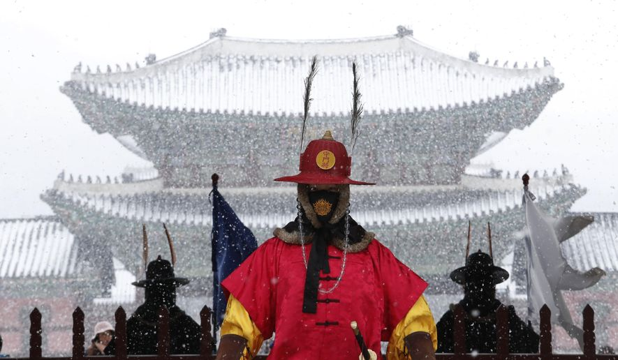 An Imperial guard wearing a face mask stands in the snow outside the Gyeongbok Palace, the main royal palace during the Joseon Dynasty in Seoul, South Korea, Monday, Feb. 17, 2020. Chinese authorities on Monday reported a slight upturn in new virus cases and hundred more deaths for a total of thousands since the outbreak began two months ago. (AP Photo/Ahn Young-joon)