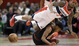 Cleveland Cavaliers guard Darius Garland, bottom, and Washington Wizards guard Bradley Beal are unable to come up with the ball during the second half of an NBA basketball game Friday, Feb. 21, 2020, in Washington. Garland was called for a foul on the play. The Cavaliers won 113-108. (AP Photo/Nick Wass) ** FILE **