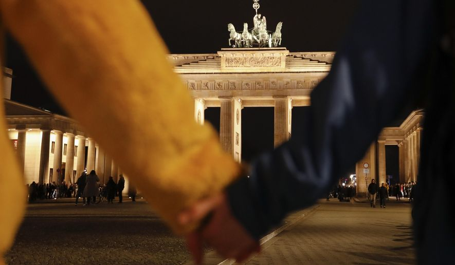 "People hold hands as they form a human chain, during a vigil for victims of last night's shooting in the central German town Hanau, at the Brandenburg Gate in Berlin, Germany, Thursday, Feb. 20, 2020. A 43-year-old German man who posted a manifesto calling for the ""complete extermination"" of many ""races or cultures in our midst"" shot and killed several people of foreign background on Wednesday night, most of them Turkish, in an attack on a hookah bar and other sites in a Frankfurt suburb, authorities said Thursday. (AP Photo/Markus Schreiber)"