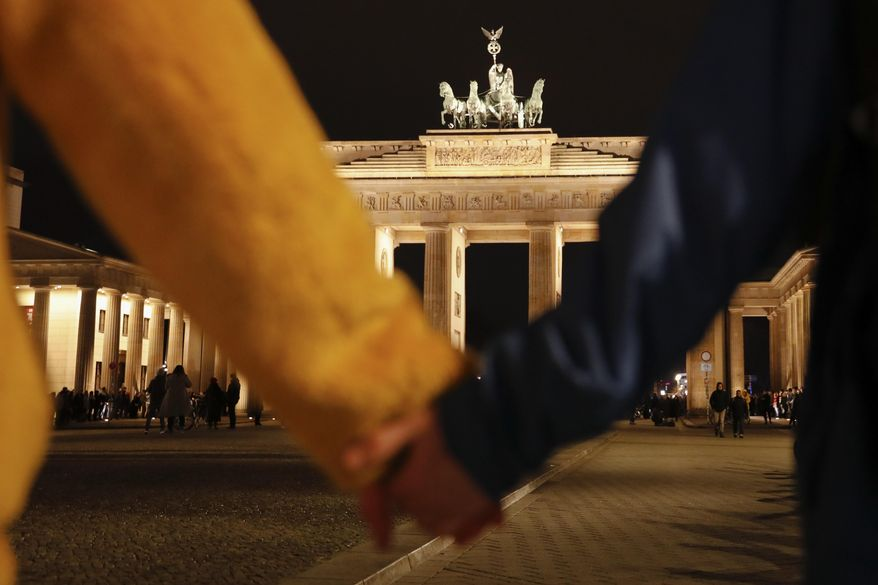 """People hold hands as they form a human chain, during a vigil for victims of last night's shooting in the central German town Hanau, at the Brandenburg Gate in Berlin, Germany, Thursday, Feb. 20, 2020. A 43-year-old German man who posted a manifesto calling for the """"complete extermination"""" of many """"races or cultures in our midst"""" shot and killed several people of foreign background on Wednesday night, most of them Turkish, in an attack on a hookah bar and other sites in a Frankfurt suburb, authorities said Thursday. (AP Photo/Markus Schreiber)"""