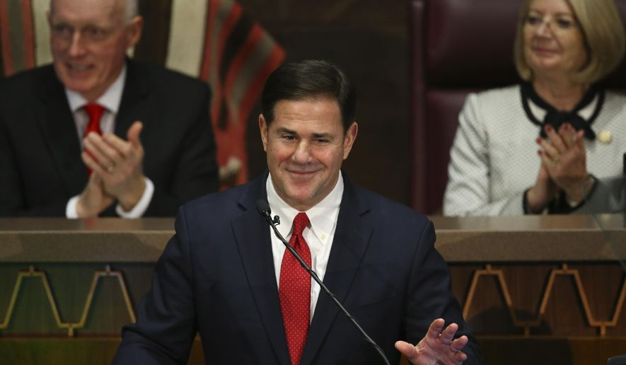 """FILE - In this Jan. 13, 2020 file photo Arizona Republican Gov. Doug Ducey, foreground, gestures during his State of the State address as Senate president Karen Fann, R-Prescott, right, and House Speaker Rusty Bowers, R-Mesa, left, listen in on the opening day of the legislative session at the Capitol in Phoenix. Ducey and Republican lawmakers have pulled a contentious proposal to enshrine a ban on so-called """"sanctuary cities"""" in the state constitution. The decision announced late Thursday, Feb. 20, 2020, comes on the eve of a House hearing on the proposal the Republican governor asked lawmakers to send to voters. (AP Photo/Ross D. Franklin,File)"""