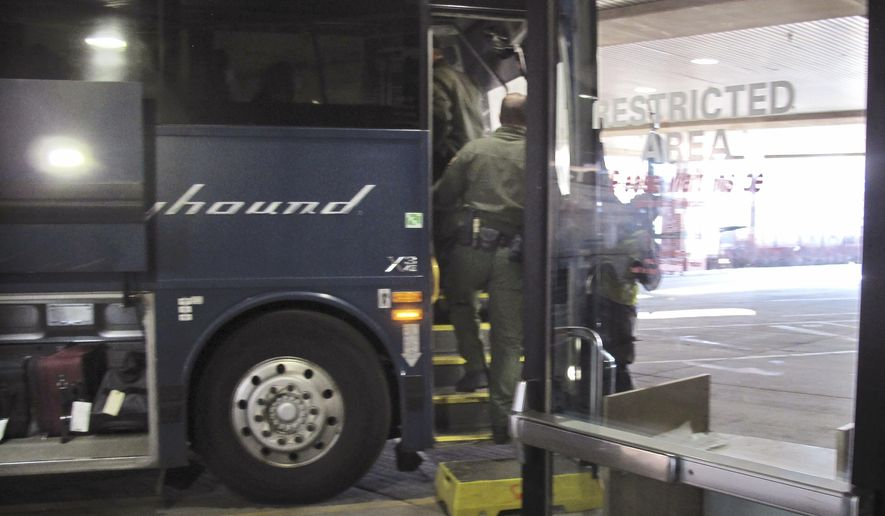 In this Thursday, Feb. 13, 2020 file photo, agents for Customs and Border Protection board a Greyhound bus headed for Portland, Ore., at the Spokane Intermodal Center, a terminal for buses and Amtrak, in Spokane, Wash. Greyhound, the nation's largest bus company, says it will stop allowing Border Patrol agents without a warrant to board its buses to conduct routine immigration checks. The company announced the change Friday, Feb. 21, 2020, one week after The Associated Press reported on a leaked Border Patrol memo confirming that agents can't board private buses without the consent of the bus company. (AP Photo/Nicholas K. Geranios,File) **FILE**