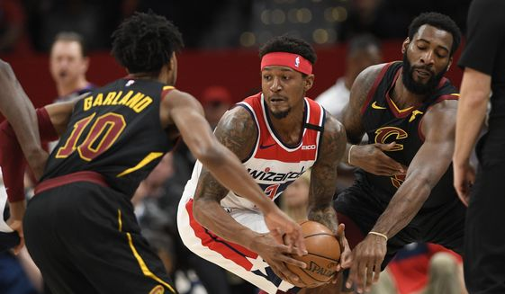 Washington Wizards guard Bradley Beal, center, handles the ball under pressure from Cleveland Cavaliers guard Darius Garland (10) and center Andre Drummond, right, during the first half of an NBA basketball game, Friday, Feb. 21, 2020, in Washington. (AP Photo/Nick Wass)