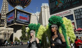 In this Feb. 19, 2020, file photo, people dressed as showgirls walk near the Paris Las Vegas hotel casino, site of a Democratic presidential debate in Las Vegas. Just past the roulette wheel and slot machines, the smoky bars and blinking lights, Nevada Democrats are preparing to weigh in on their party's presidential nomination fight. (AP Photo/John Locher, File)