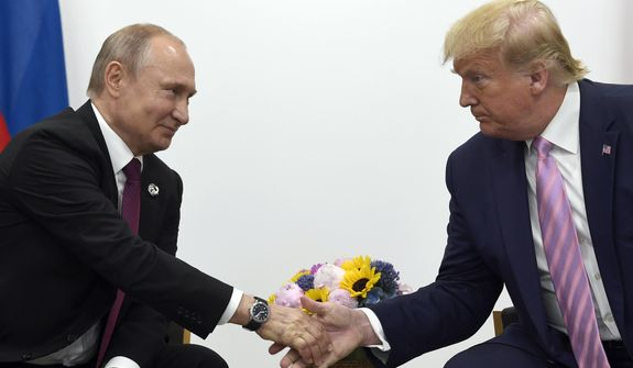 In this June 28, 2019, file photo, President Donald Trump, right, shakes hands with Russian President Vladimir Putin, left, during a bilateral meeting on the sidelines of the G-20 summit in Osaka, Japan. (AP Photo/Susan Walsh, File)