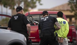 In this July 8, 2019, photo, a U.S. Immigration and Customs Enforcement (ICE) officers detain a man during an operation in Escondido, Calif. (AP Photo/Gregory Bull) **FILE**