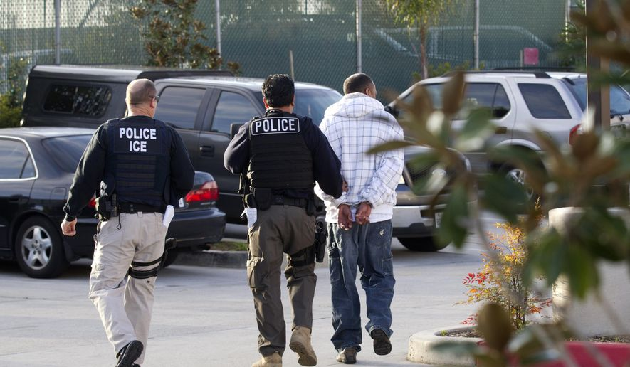 In this March 30, 2012, photo, Immigration and Customs Enforcement (ICE) agents take a suspect into custody as part of a nationwide immigration sweep in Chula Vista, Calif. (AP Photo/Gregory Bull) **FILE**