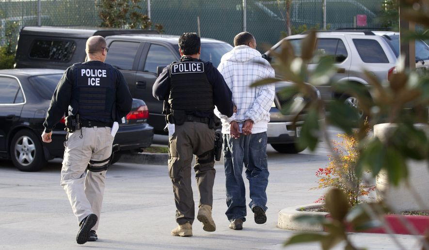 In this March 30, 2012, file photo, Immigration and Customs Enforcement (ICE) agents take a suspect into custody as part of a nationwide immigration sweep in Chula Vista, Calif. (AP Photo/Gregory Bull) ** FILE **