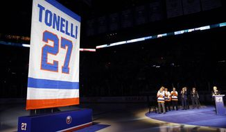 A banner with the name and number of former New York Islander Jon Tonelli is raised Friday, Feb. 21, 2020, in Uniondale, N.Y., as some of Tonelli's former teammates and an announcer, right applaud. (AP Photo/Kathy Willens)