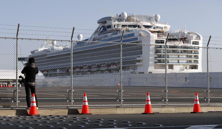 A photographer takes photos near the quarantined Diamond Princess cruise ship anchored at a port in Yokohama, near Tokyo, Friday, Feb. 21, 2020. Passengers tested negative for COVID-19 started disembarking since Wednesday. (AP Photo/Eugene Hoshiko)