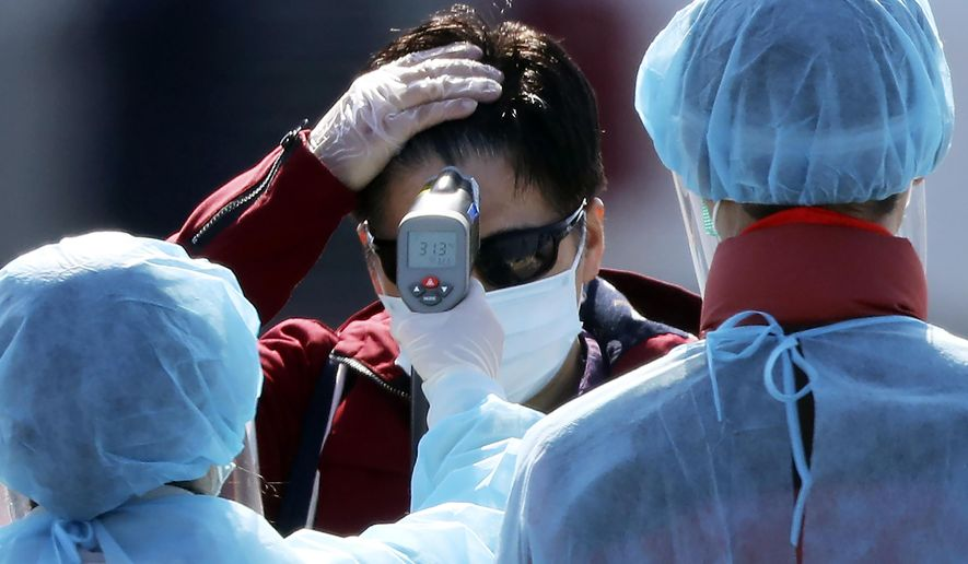 An official in protective suits measure the temperature of the foreign passengers disembarked from the quarantined Diamond Princess cruise ship before boarding to buses at a port in Yokohama, near Tokyo, Friday, Feb. 21, 2020. Passengers tested negative for COVID-19 started disembarking since Wednesday. (AP Photo/Eugene Hoshiko)