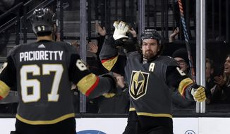 Vegas Golden Knights right wing Mark Stone, right, celebrates with left wing Max Pacioretty after scoring against the Tampa Bay Lightning during the second period of an NHL hockey game Thursday, Feb. 20, 2020, in Las Vegas. (AP Photo/Isaac Brekken)