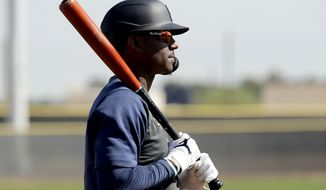 Seattle Mariners' Kyle Lewis waits to bat during spring training baseball practice Tuesday, Feb. 18, 2020, in Peoria, Ariz. (AP Photo/Charlie Riedel)