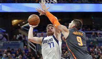Dallas Mavericks guard Luka Doncic (77) shoots over Orlando Magic center Nikola Vucevic (9) during the first half of an NBA basketball game, Friday, Feb. 21, 2020, in Orlando, Fla. (AP Photo/John Raoux)