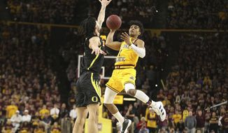 Arizona State's Remy Martin (1) looks for an open teammate as Oregon's Addison Patterson (22) defends during the second half of an NCAA college basketball game Thursday, Feb. 20, 2020, in Tempe, Ariz. (AP Photo/Darryl Webb)