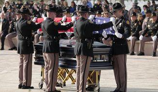 Folding of the American flag for slain Florida Highway Patrol Trooper Joseph Bullock at Sarasota National Cemetery on Thursday, Feb. 13, 2020. Trooper Bullock was shot and killed in the line of duty last week when he stopped to help a motorist. (Thomas Bender/Sarasota Herald-Tribune via AP)